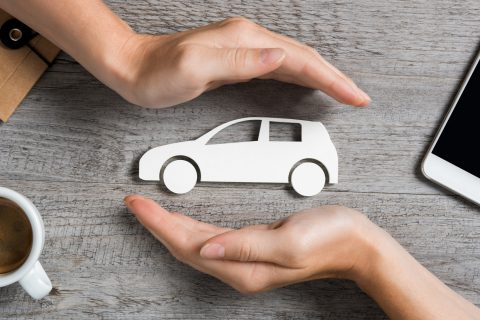 hands protecting cutout of white car